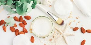Top view white cosmetic product ingredients, homemade rice water and nut milk facial lotion with almond.