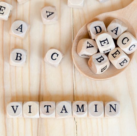 Top views vitamin word made from wooden letters on the table and A B C D E on the wood spoon, Health concept