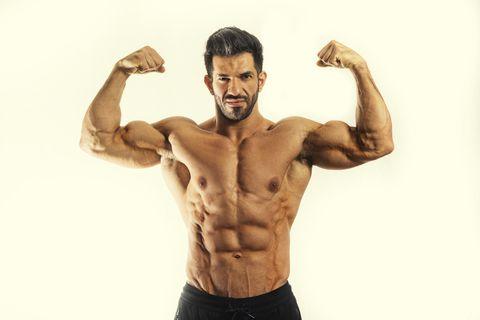 Topless male body builder flexing biceps
