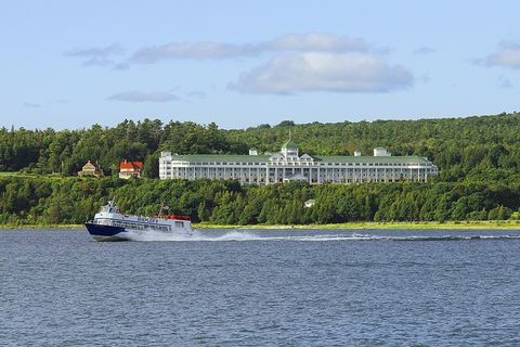 A tour boat speeds past the Grand Hotel