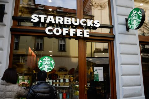 Tourists stand in front of a Starbucks coffee.   Prague the...