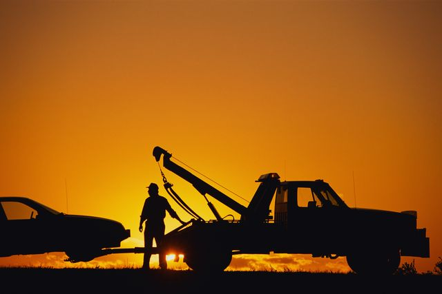 tow truck operator at sunset