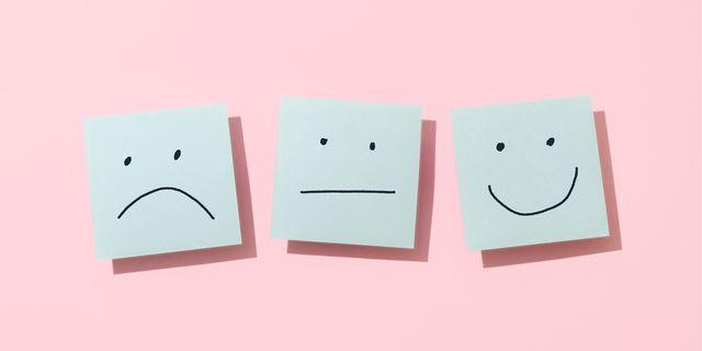 die notitieblaadjes met een ongelukkig, neutraal en lachend gezichtje getekend op een roze achtergrond