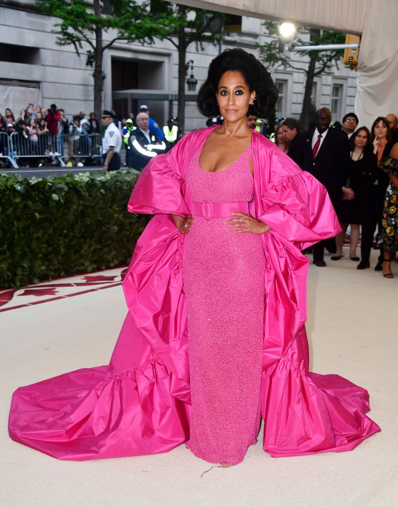The Blackish star donned a belted and beaded shocking pink Michael Kors Collection gown with an elaborate train for the 2018 Met Gala.