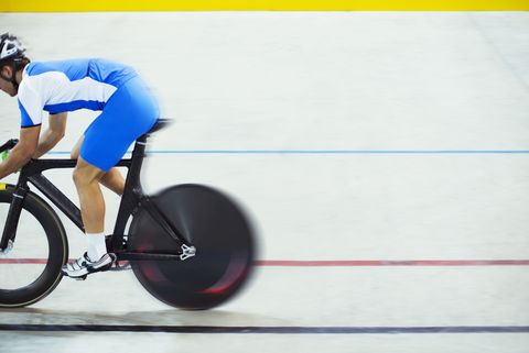 Track cyclist riding in velodrome
