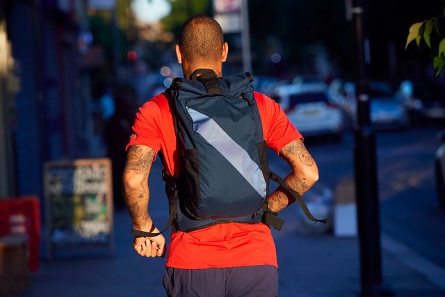 a man in a red t shirt and navy backpack running