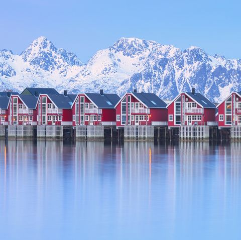 traditional wood houses called rorbu in the fishing village of svolvaer surrounded by cold sea and snowcapped mountains at dusk, lofoten islands, norway