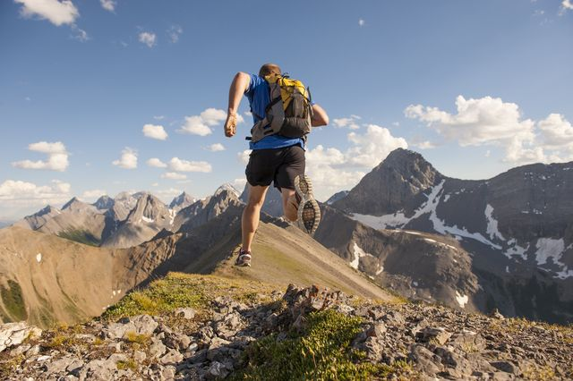 trail runner corriendo con una mochila en mitad de dos montañas