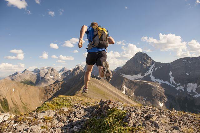 trail runner in mid air stride, on mountain ridge