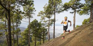 Trail runner running on dirt path near forest, Fuencaliente, La Palma, Canary Islands, Spain
