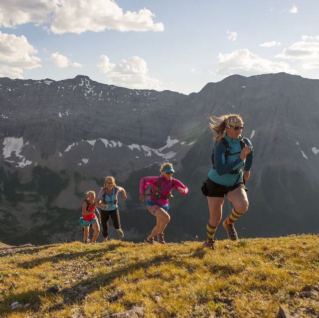 Trail runners in mid air stride towards mtn summit