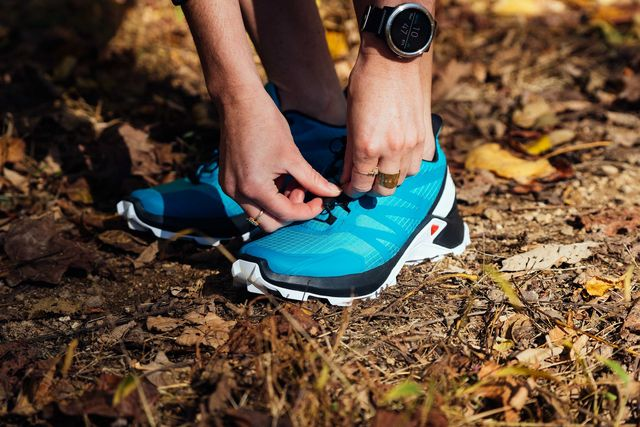 trail running shoes being tied on trail path