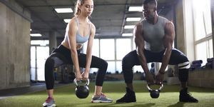 Trainer and female client exercise with kettlebells in gym