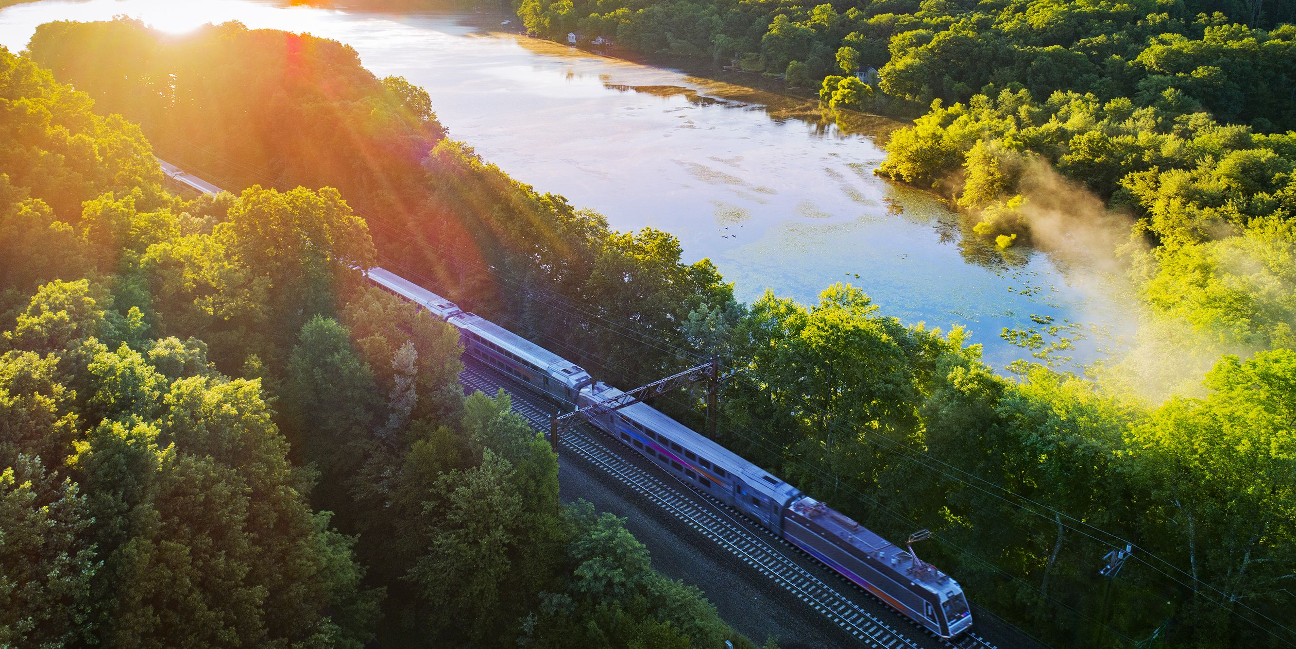 Aerial view of train passing by Estling Lake on sunny day