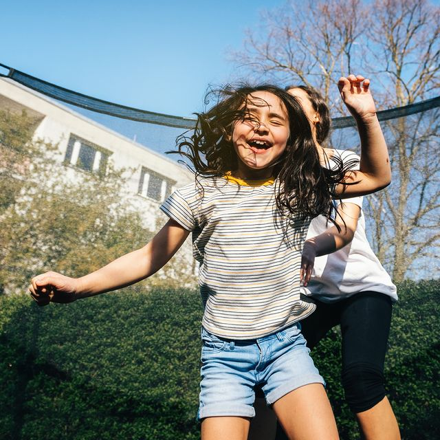 girls jumping on trampoline with net