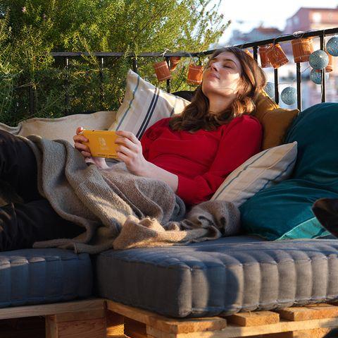 chica descansando en su terraza después de jugar con la nintendo switch a anima crossing new horizons