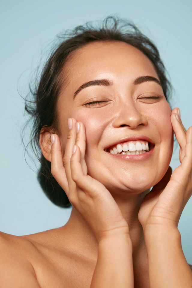 skin care woman with beauty face touching healthy facial skin portrait beautiful smiling asian girl model with natural makeup touching glowing hydrated skin on blue background closeup
