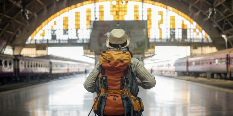 traveler man waits train on railway platform.