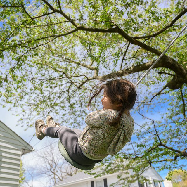 young girl playing on tree swing