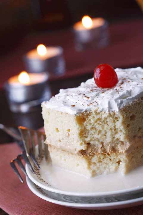tres leches cake with cinnamon and a cherry partially eaten