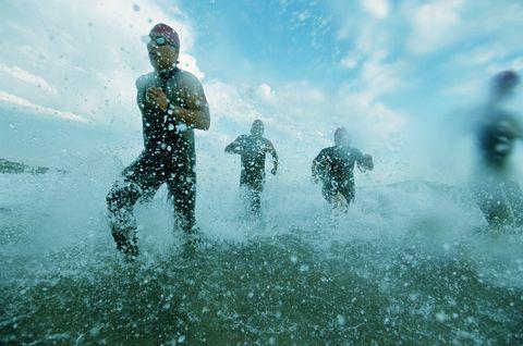 Tri-atheletes running on surf