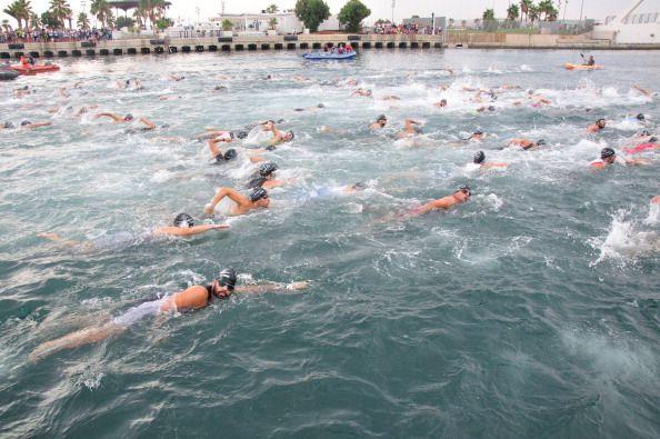 varios triatletas nada en el mar mediterráneo en el triatlón de valencia