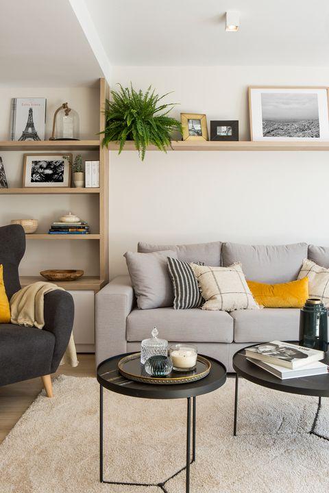 salón decorado en tonos neutros con dos mesas nido redondas en color negro