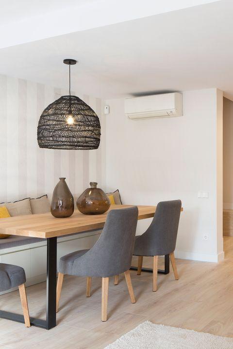 comedor abierto con mesa de madera y sillas tapizadas en gris