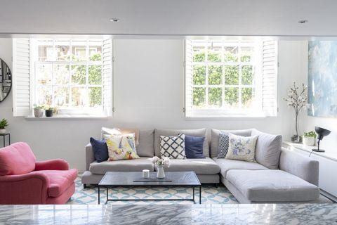 salón abierto con sofá en l gris y butaca color coral