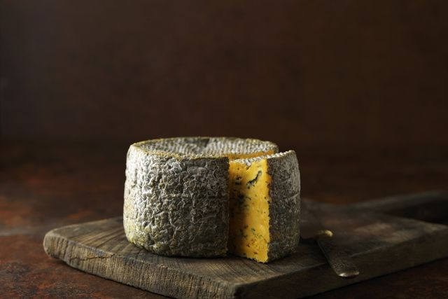 truckle of blacksticks blue cheese on chopping board