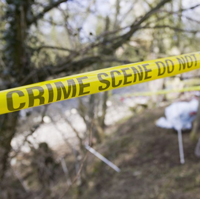 Yellow crime scene tape in front of a murder scene being investigated by police.