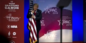 U.S. President Donald Trump hugs a U.S. flag as he takes the stage at CPAC in National Harbor, Maryland