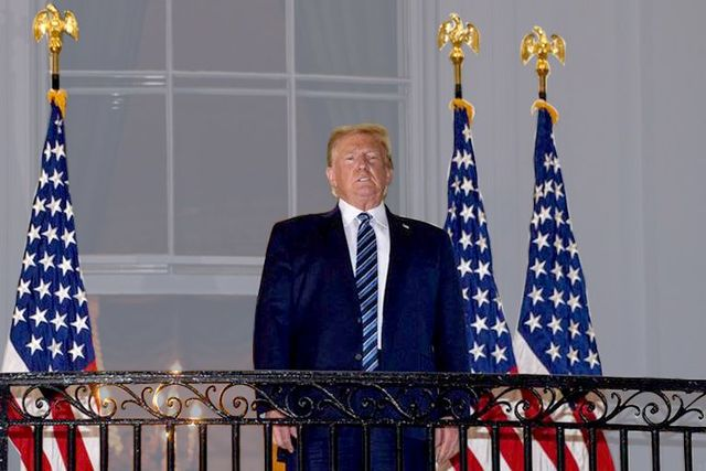 us president donald trump looks out from the truman balcony as he arrives at the white house upon his return from walter reed medical center, where he underwent treatment for covid 19, in washington, dc, on october 5, 2020 photo by nicholas kamm  afp photo by nicholas kammafp via getty images