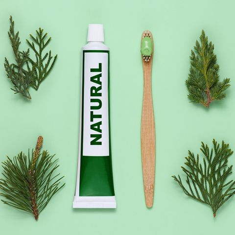 Tube of natural toothpaste and bamboo toothbrush on green background