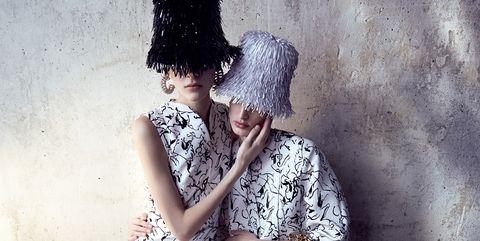 Clothing, Leg, Hat, Human leg, Dress, Sitting, One-piece garment, Toe, Fashion, Black,