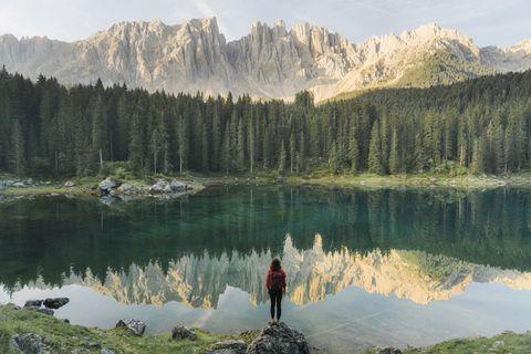 mujer ante el lago di carezza en los dolomitas