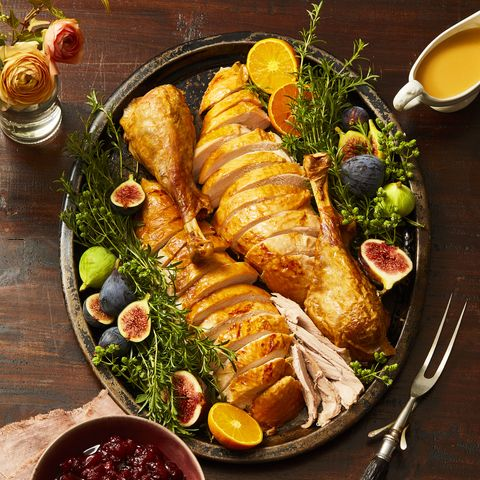 turkey cut into pieces on platter with cranberry sauce and gravy