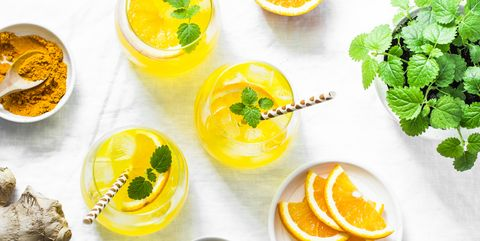 Turmeric, ginger, orange lemonade. Summer cold drink on light background, top view. Flat lay