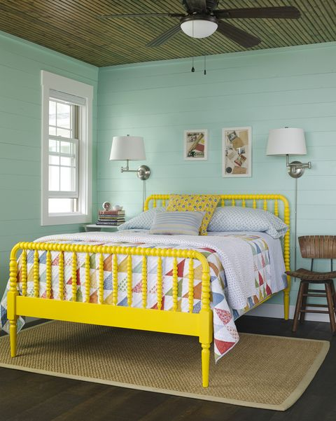 bedroom with turquoise walls and yellow bed