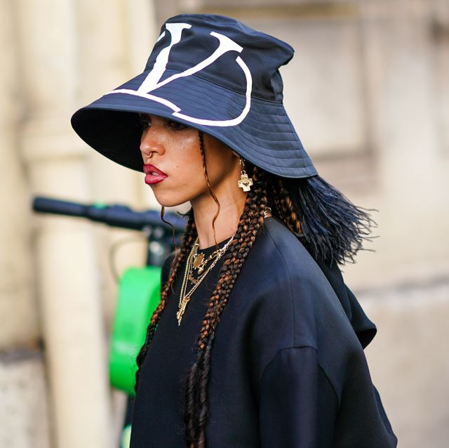 fka twigs draagt een grote zwarte bucket hat van valentino met logo en een zwart t shirt met kettingen en oorbellen