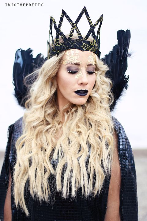 woman with long blonde hair dressed as queen ravenna with black lips, gold makeup and a black and gold crown
