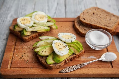 two avocado sandwiches with egg and spices on a wooden Board
