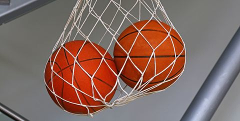Two basketball balls hanging in mesh sack