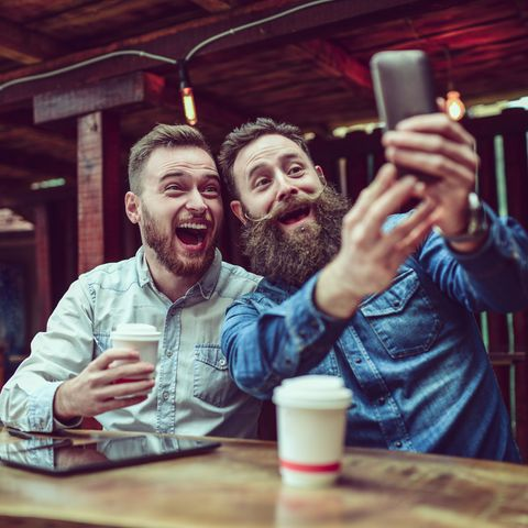 Two Bearded Friends Drinking Coffee and Taking Selfie in Restaurant