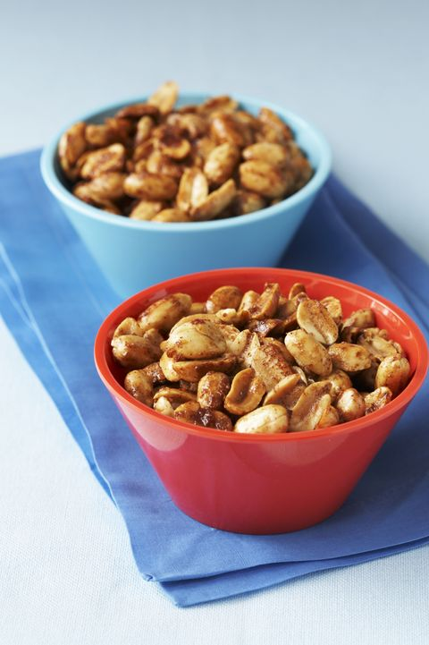 two bowls of mixed spiced nuts on blue napkins