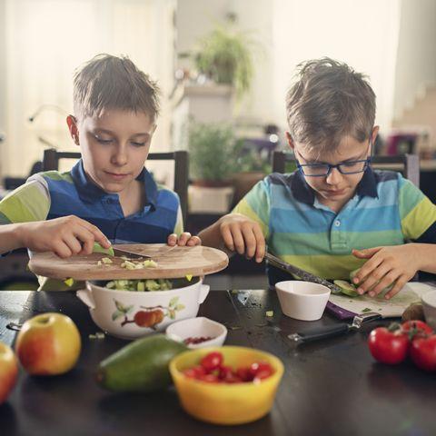 two boys making vegan salad at home