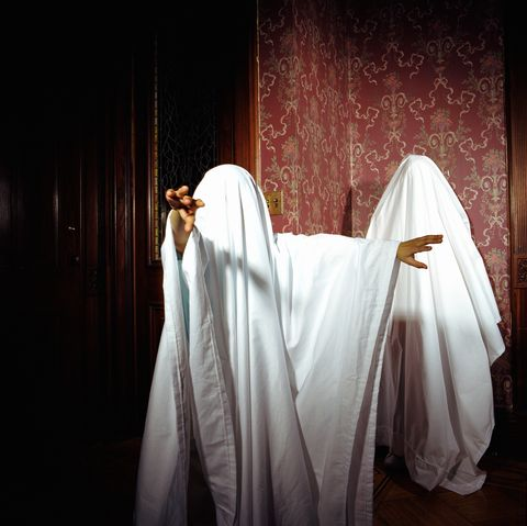 Two childen (7-9) playing ghost, wearing sheets