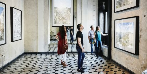 two couples admiring artwork while touring museum during vacation