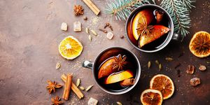 Two cups of christmas mulled wine or gluhwein with spices and orange slices on rustic table top view. Traditional drink on winter holiday.