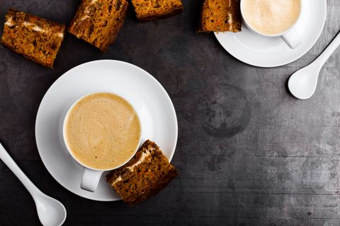 two cups of fresh cappuccino with slice of carrot cake